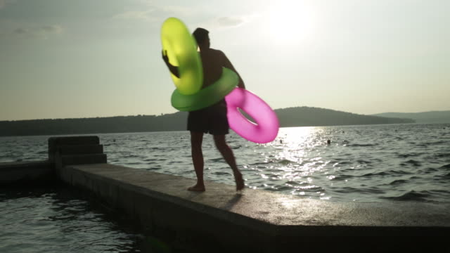 man walks into shot and along jetty carrying colorful inflatable rings. - ブラック島点の映像素材/bロール