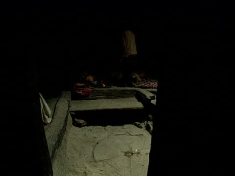 vídeos de stock, filmes e b-roll de man walks into squalid shack lays next to other addict and pulls on opium pipe afghanistan - abuso de substâncias
