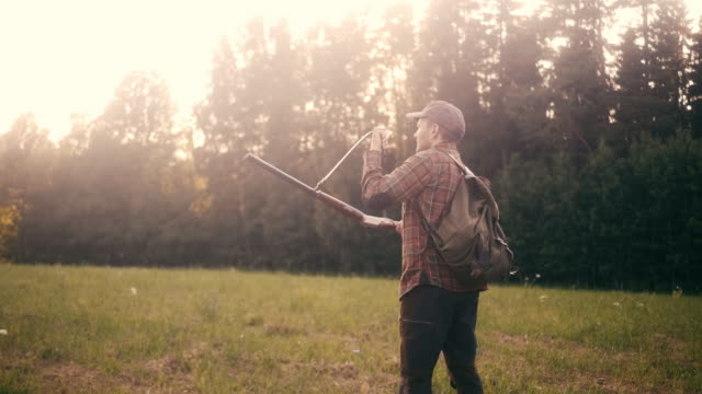 stockvideo's en b-roll-footage met man loopt in het frame en schiet met shotgun (slow motion) - vogeljacht