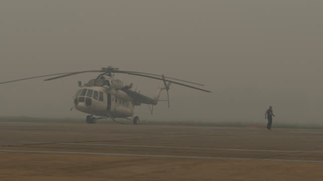 a man walks near mi17 water bombing at tjilik riwut airport as haze from the forest fires blankets the area in palangkaraya city on september 14 2019... - kalimantan stock videos and b-roll footage