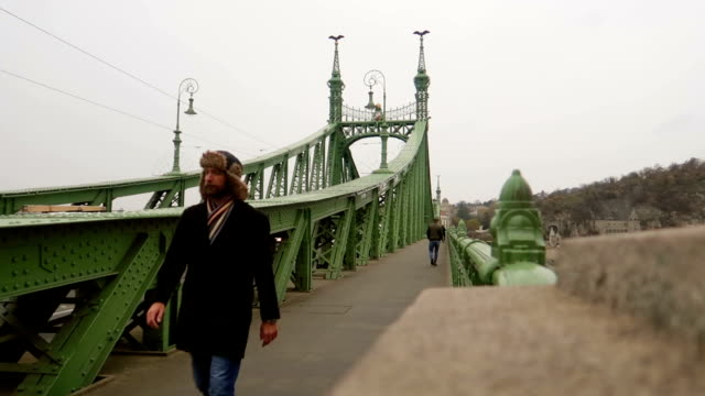 man walks on a bridge - stock video - széchenyi chain bridge stock videos & royalty-free footage