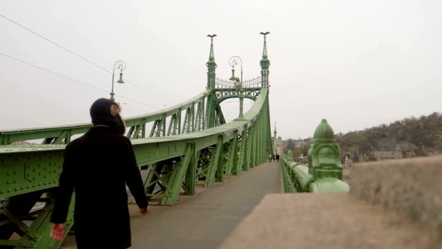 man walks on a chain bridge - budapest - stock video - széchenyi chain bridge stock videos & royalty-free footage