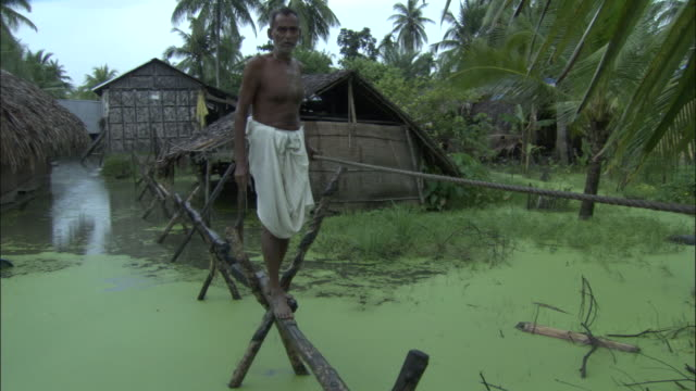 vídeos de stock, filmes e b-roll de a man walks on a raised beam over flood waters. available in hd. - bangladesh