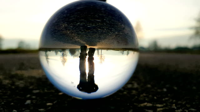 man walks on country road at sunset - filmed through a crystal ball - glass material stock videos & royalty-free footage