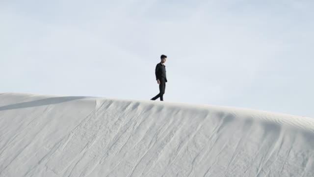 man walks on sand dunes in desert, medium shot - extreme terrain stock videos & royalty-free footage