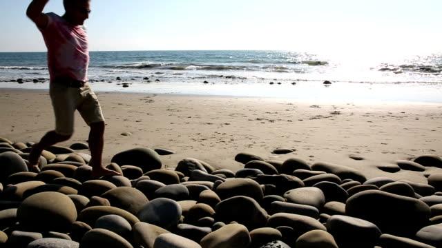 vidéos et rushes de homme marchant sur shoreline rocks - sortir du lot