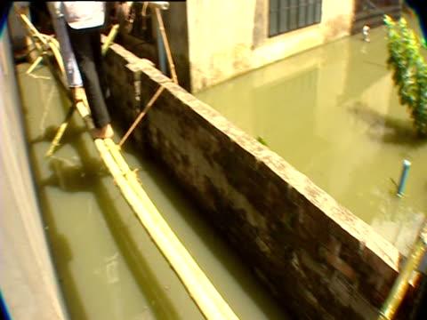 man walks on sticks to avoid flood waters - bangladesch stock-videos und b-roll-filmmaterial