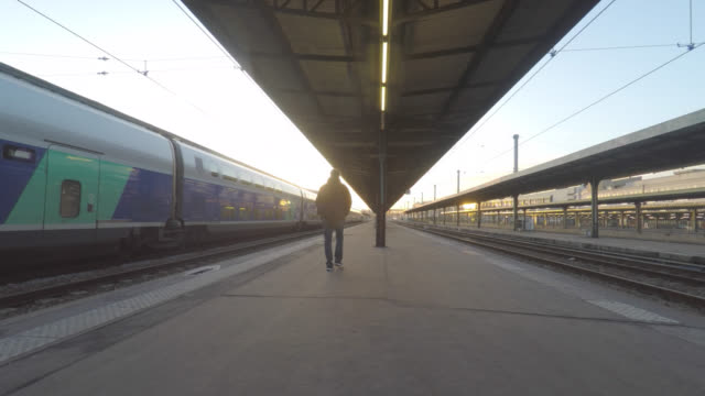 man walks on the platform of a train station