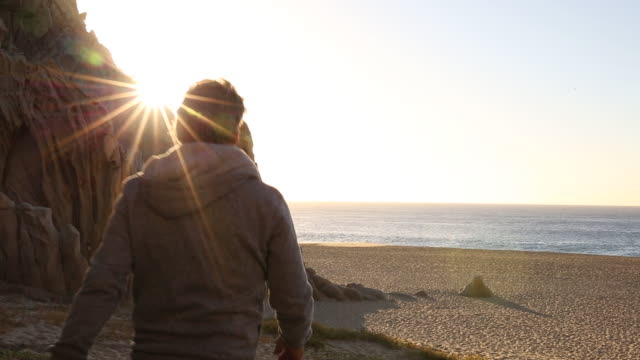 Man walks onto beach at sunrise, looking out to sea