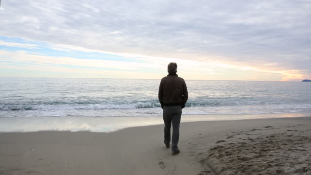 man walks onto beach by sea edge, continues along beach - standing stock videos & royalty-free footage