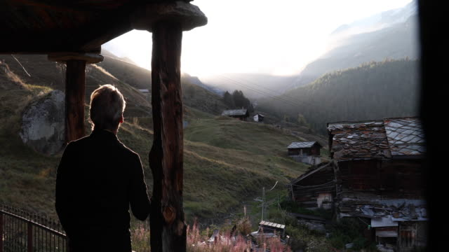 man walks onto chalet verada with hot drink, looks off - chalet stock videos & royalty-free footage