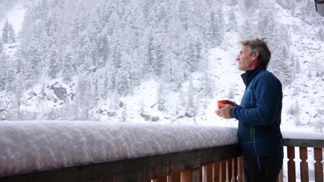 Man walks onto chalet veranda with hot drink, snowstorm