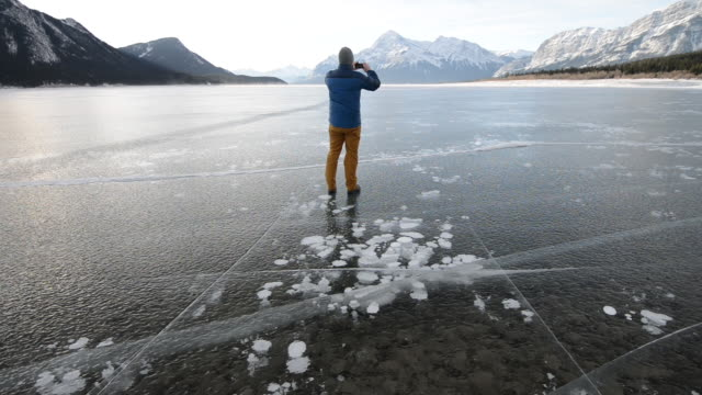 Man walks onto frozen lake, takes smart phone pic
