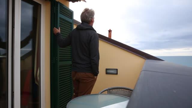 Man walks onto hotel veranda, looks out to sea