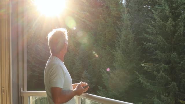 vídeos de stock e filmes b-roll de man walks onto outdoor deck holding smart phone - 60 64 anos