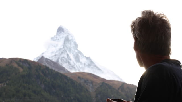 Man walks onto veranda with hot beverage, below Matterhorn
