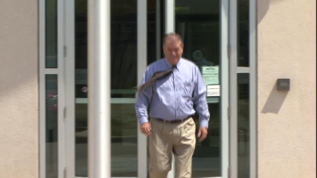 vídeos de stock, filmes e b-roll de a man walks out of a federal building. - cruzar