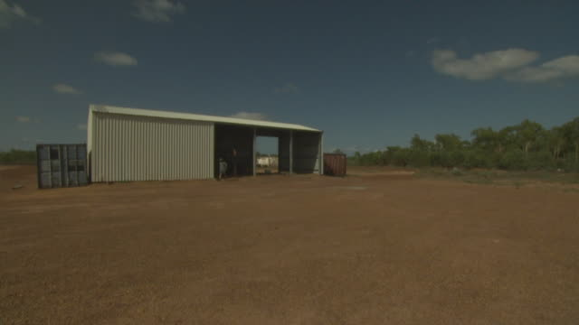man walks out of corrugated shed in outback, australia - shed stock videos & royalty-free footage