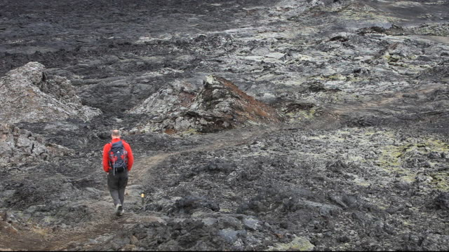 A man walks over a lava flow still steaming near Myvatn in Iceland.