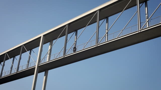 stockvideo's en b-roll-footage met man walks over a modern bridge - brug mens gemaakte bouwwerken