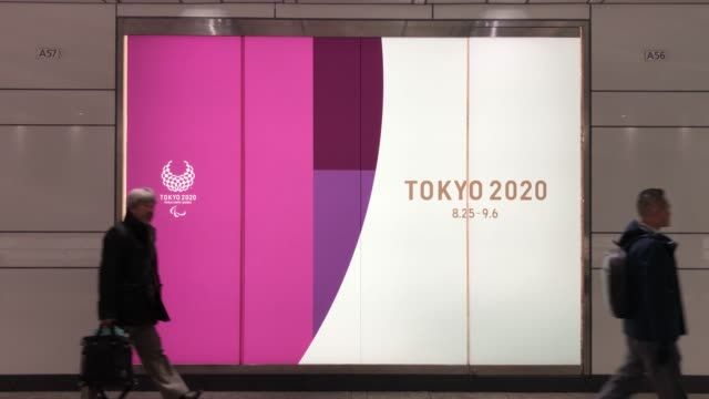 man walks past an advert for the tokyo 2020 olympics on march 25, 2020 in tokyo, japan. following yesterdays announcement that the tokyo 2020... - オリンピック大会点の映像素材/bロール