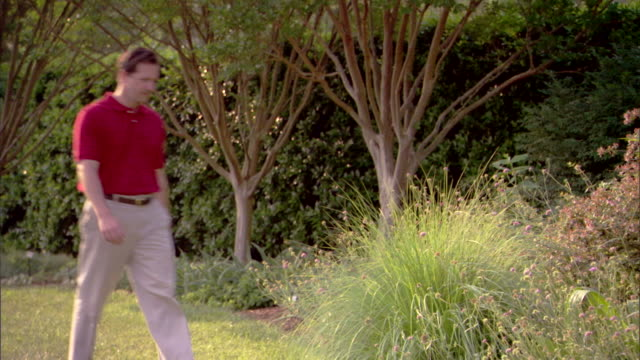 A man walks past bushes and flowers in a botanical garden.