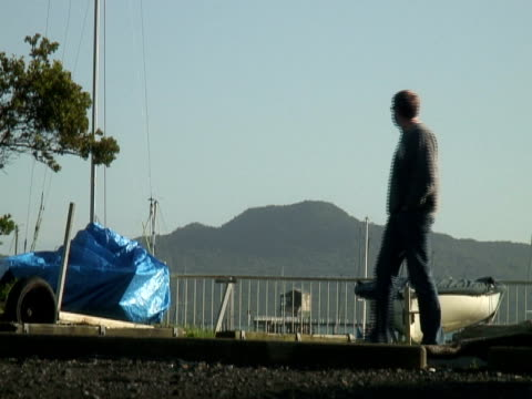 Man Walks Past Dry-docked Boats