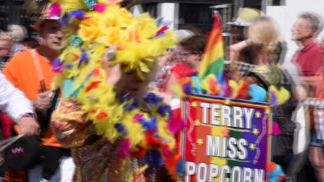 man walks past the camera carrying a sign whilst wearing a distinctive gold and yellow feathered costume in the brighton gay pride parade 2017, in... - イーストサセックス点の映像素材/bロール