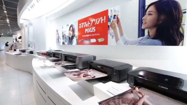 a man walks past the canon inc logo displayed outside the company's showroom in tokyo japan on monday jan 25 a man walks past the entrance to the... - digital camera stock videos and b-roll footage