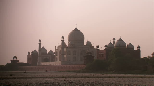 a man walks past the taj mahal at sunrise. - onion dome stock videos and b-roll footage