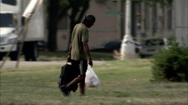a man walks past two homeless seniors in a city park. available in hd. - detroit michigan stock videos & royalty-free footage