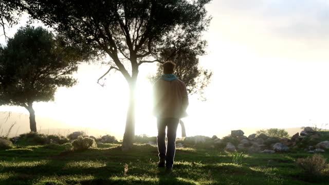 Man walks through forested glade towards sunrise