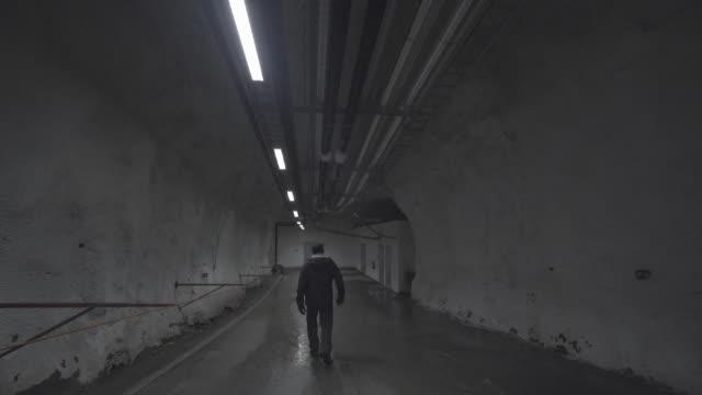 man walks through global seed vault tunnel, wide shot from behind - スヴァールバル諸島点の映像素材/bロール