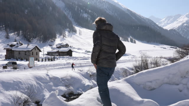 man walks through snow, enjoys view up mountain creek - down jacket stock videos and b-roll footage