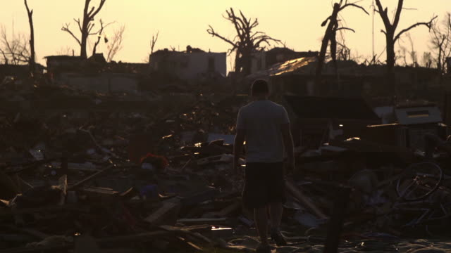 stockvideo's en b-roll-footage met man walks through tornado damage silohette - beschadigd