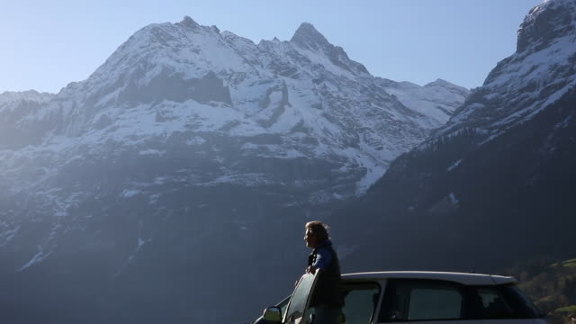 Man walks to car, then looks off to mountain view, from roadside
