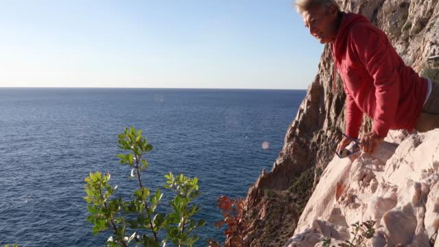 男は崖の端、はるか下の海を歩く - 中年の男性だけ点の映像素材/bロール