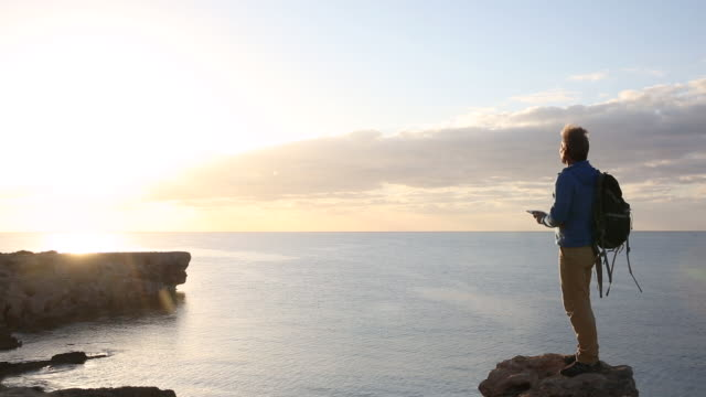 Man walks to cliff edge, takes pic with digital tablet