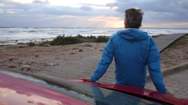 man walks to front hood of car, watches sunset over sea - kopfbedeckung stock-videos und b-roll-filmmaterial