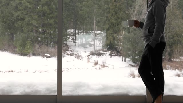 man walks to living room window with hot drink - cold temperature stock videos & royalty-free footage