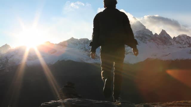 vídeos y material grabado en eventos de stock de man walks to mtn ridge crest, holds arms out, then walks onwards - miembro humano