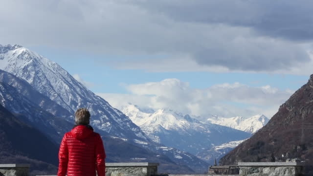 Man walks toward mountain viewpoint a, looks out to view
