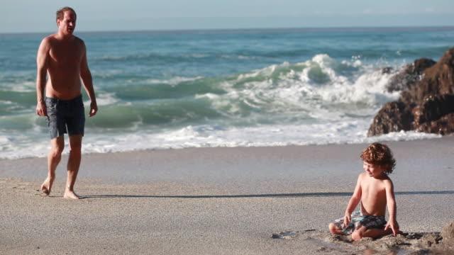 ms ts td man walks towards boy on beach and hands him shell  / montezuma, puntarenas, costa rica - kelly mason videos stock videos & royalty-free footage