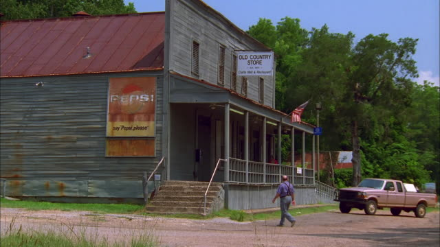 Man walks towards store and climbs steps to porch, Natchez, Mississippi Available in HD.