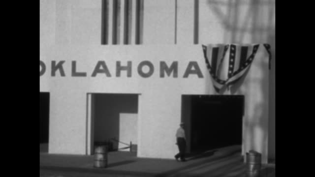 vidéos et rushes de ms man walks up stairs between pumpjacks and american flags / pan exterior exhibit hall with oklahoma and bunting on it as man walks in / people... - actualités cinématographiques