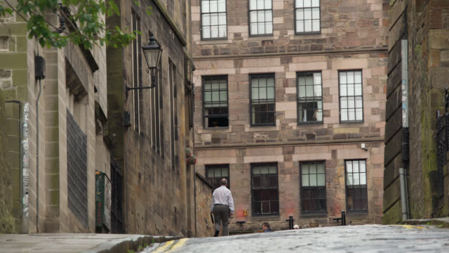 man walks up steep road in edinburgh old town - steep stock videos & royalty-free footage
