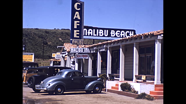 man walks up steps at the malibu inn beach stores 1939 / cars parked outside - surfing stock videos & royalty-free footage
