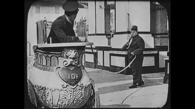 1917 man (fatty arbuckle) walks up to ticket clerk at coney island before walking away with strip of tickets attached - ticket stock videos & royalty-free footage
