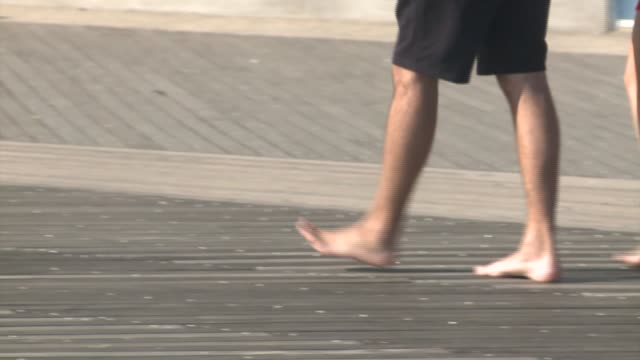 stockvideo's en b-roll-footage met a man walks with bare feet down the boardwalk in coney island on a warm october day unseasonably warm october day in new york city on october 18 2016... - blootvoets