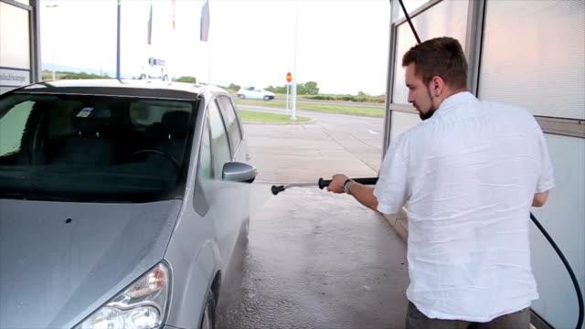 Een man wast zijn auto